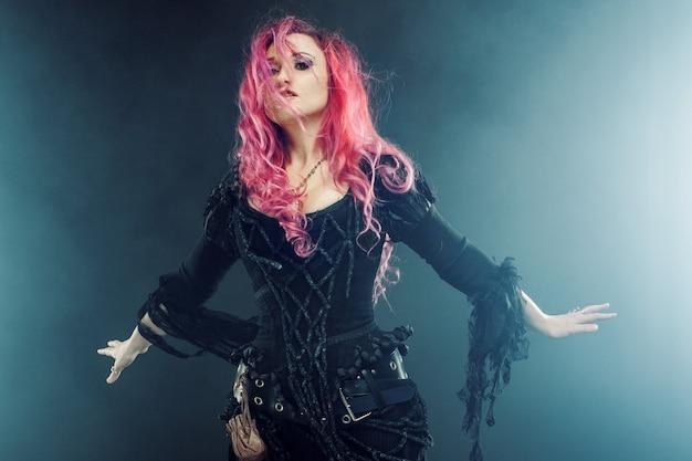 La bruja crea magia. mujer con el pelo rojo en traje de brujas