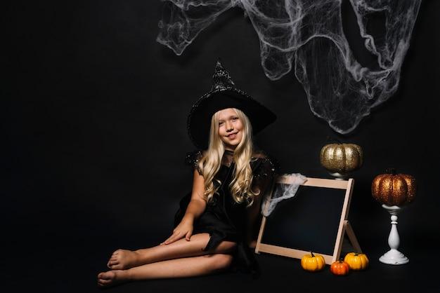 Bruja descalza cerca de la pizarra y decoraciones de halloween