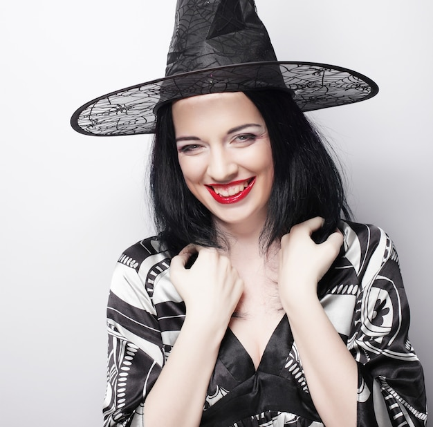 Bruja divertida. mujer joven feliz con sombrero canival. tiro del estudio.
