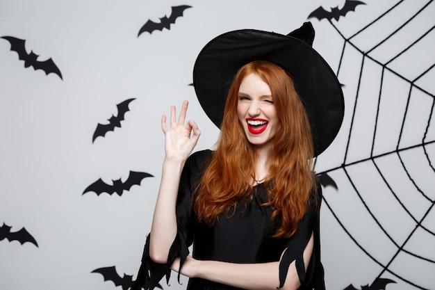 Bruja feliz del pelo del jengibre de halloween que lleva a cabo la muestra aceptable con los dedos que presentan sobre fondo gris.