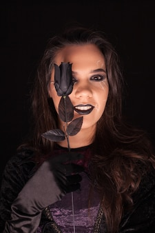 Bruja gótica con una rosa sobre fondo negro. disfraz de halloween.