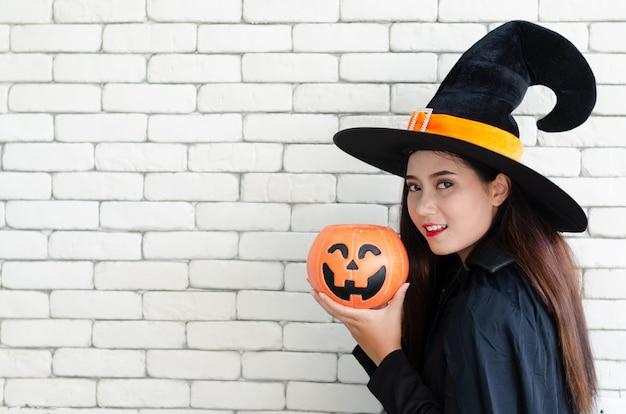 Bruja de halloween con una calabaza mágica, hermosa mujer joven con sombrero de brujas y disfraz