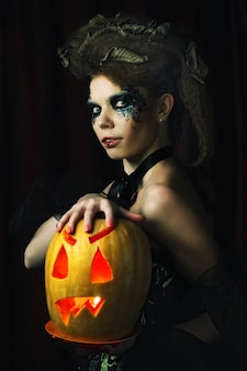 Bruja de halloween con calabaza tallada sobre fondo rojo.