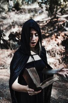Bruja de halloween diciendo palabras de hechizo en el bosque durante el día