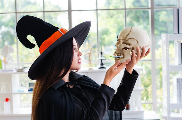 Bruja de halloween, hermosa mujer joven con sombrero de brujas y disfraz