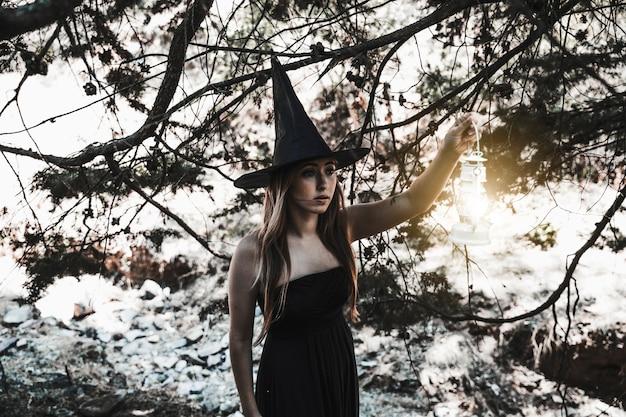 Bruja de halloween iluminando el camino en el bosque