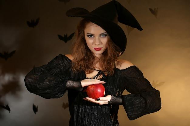 Bruja de halloween con manzana en superficie oscura