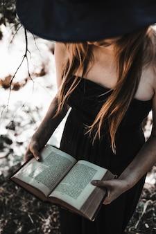 Bruja de halloween que sostiene el libro de conjuros antiguo en maderas iluminadas por el sol