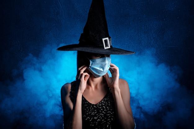 Bruja de halloween con sombrero negro y máscara facial.