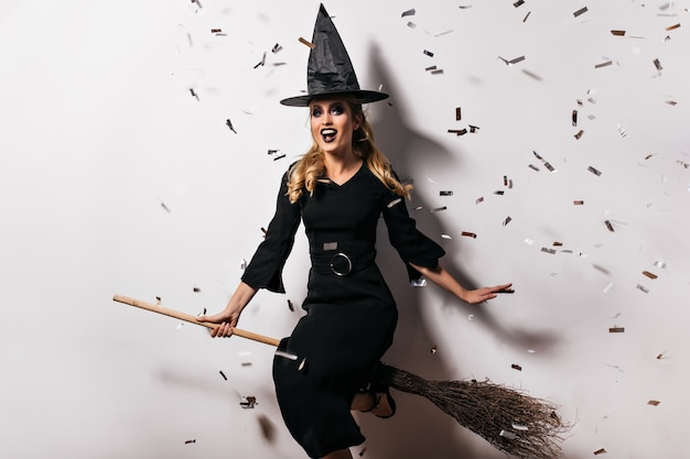 Bruja joven bien formada en traje negro sentada en una escoba. filmación en interiores de lindo mago viste sombrero y vestido largo en la fiesta de halloween.