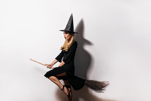 Bruja joven soñadora volando en escoba en halloween. filmación en interiores del elegante mago rubio posando en la pared blanca.