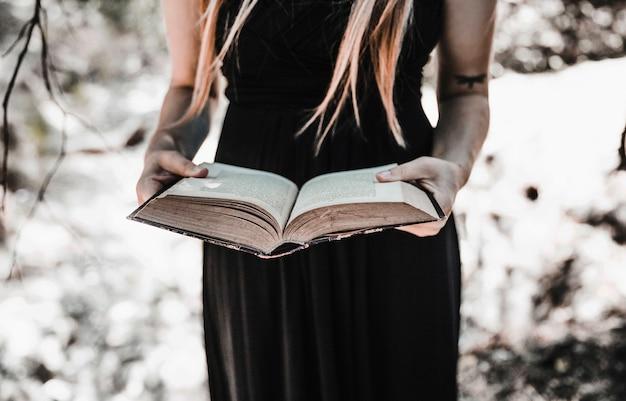 Bruja con libro envejecido en bosque soleado