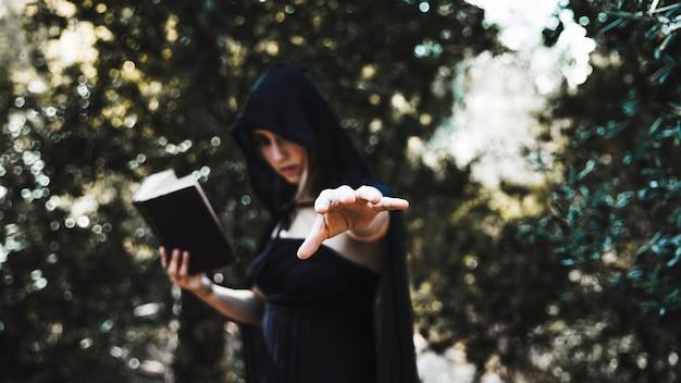 Bruja con libro usando magia en matorral