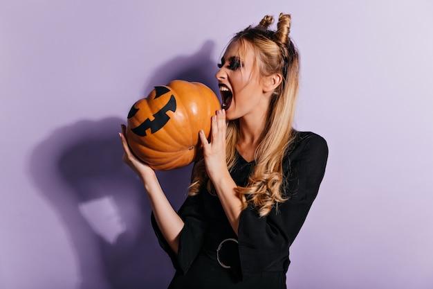 Bruja de moda gritando en la pared púrpura. magnífica chica vampiro mirando calabaza.