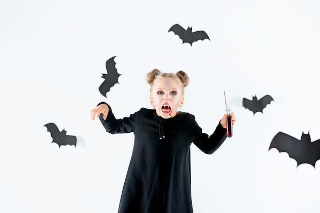 Bruja niña en vestido largo negro y accesorios mágicos.