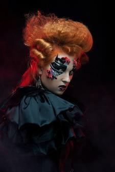 Bruja pelirroja gótica. mujer morena. maquillaje artístico. cuadro de halloween.