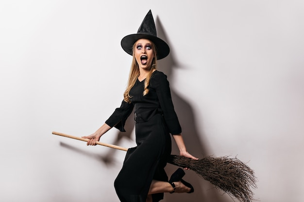 Bruja sorprendida con maquillaje negro posando en halloween. encantadora dama rubia con sombrero mágico con escoba.