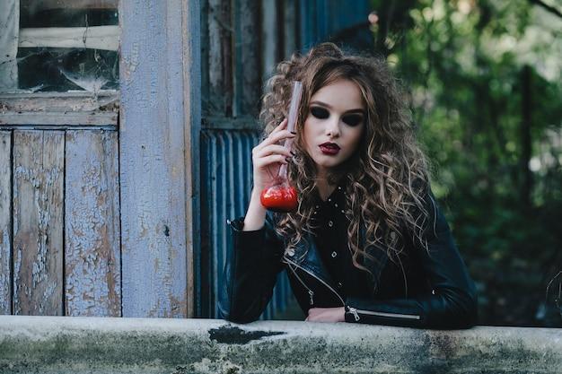 La bruja vintage realiza un ritual mágico, con elixir en la mano, en vísperas de halloween.