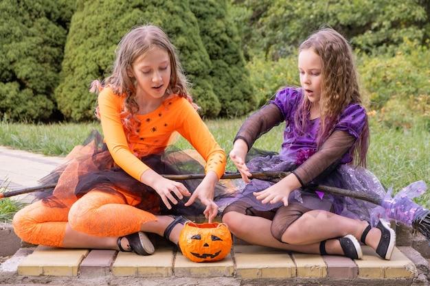 Brujas de disfraces de halloween para niños y niñas conjurando una calabaza