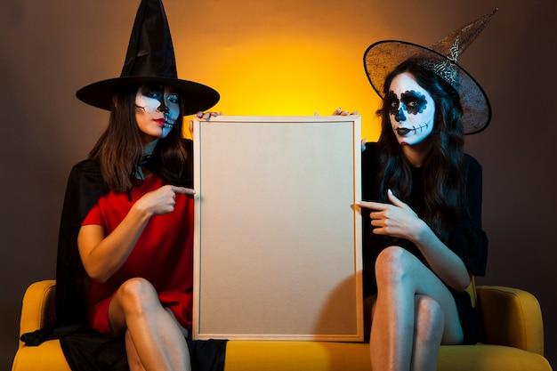 Brujas jóvenes sujetando pizarra blanca