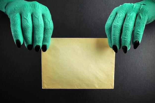 Brujas verdes de halloween o manos de monstruo zombie sosteniendo papel en blanco