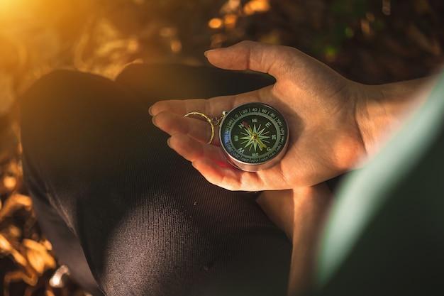 Brújula en el bosque, de la mano con la vieja brújula para la navegación en el bosque