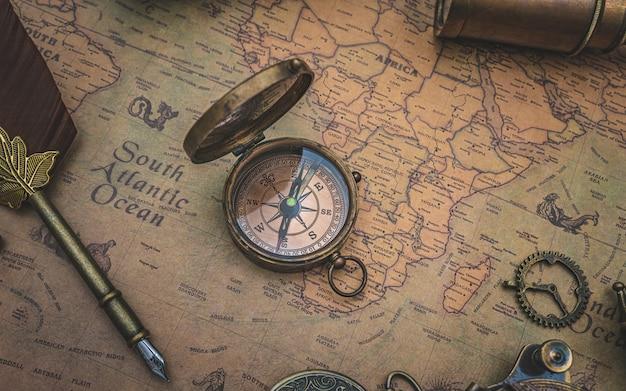 Brújula de bronce antiguo con tapa en el mapa del viejo mundo