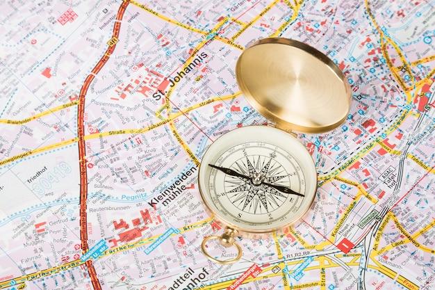 Brújula closeup sobre fondo de mapa de la ciudad