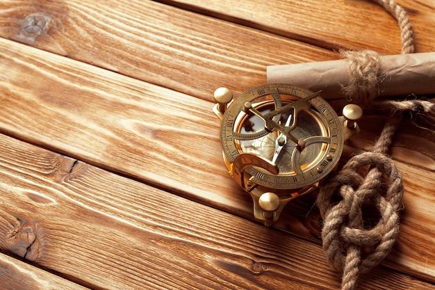Brújula y cuerda sobre tablas de madera viejas.