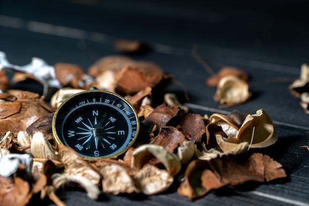 Brújula dorada puesta en hojas secas en mesa retro de madera negra