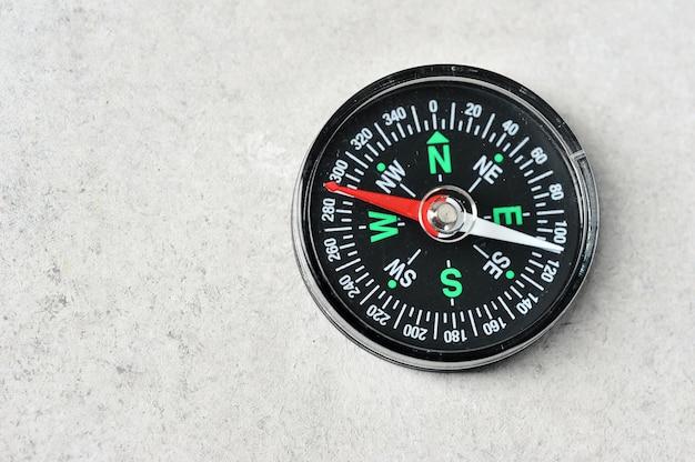 Brújula con una flecha roja magnética sobre un fondo gris con espacio para texto