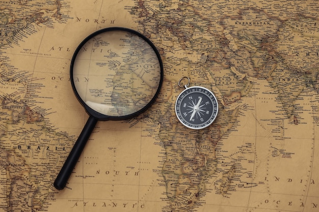 Brújula y lupa en mapa antiguo. viajes, concepto de aventura