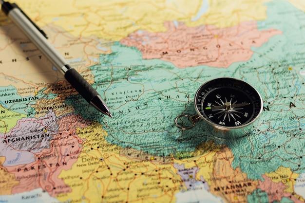 Brújula magnética y pluma en el mapa.