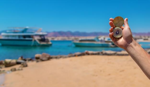 Brújula en mano contra el fondo del mar. enfoque selectivo. naturaleza.