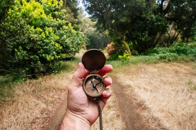 Una brújula en la mano de un hombre con un camino