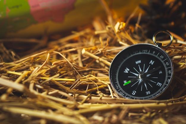 Brújula con mapas de papel y flores de pino colocadas sobre paja de trigo seco a la luz del sol de la mañana.