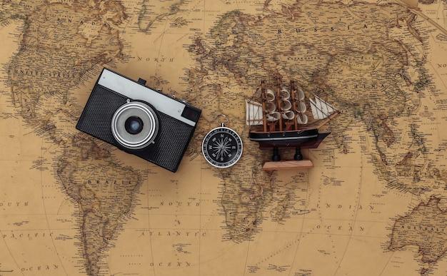 Brújula y nave, cámara en mapa antiguo. viajes, concepto de aventura