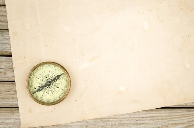 Brújula y papel viejo sobre fondo de madera