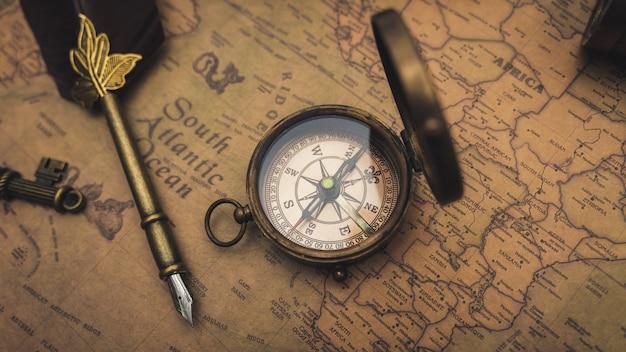 Brújula y pluma en el mapa antiguo