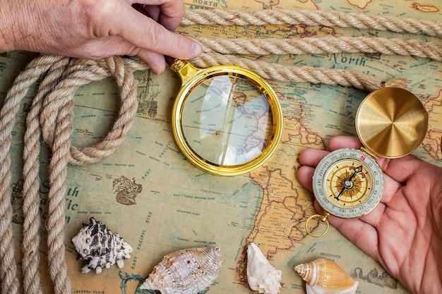 Brújula retro vintage antiguo, lupa en el mapa del mundo antiguo