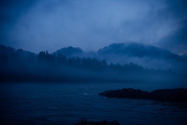 Bruma azul, mística mañana brumosa. fantástico paisaje, espesa niebla sobre un río de montaña al anochecer.