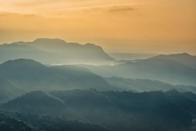 Brumoso en las montañas con espectacular cielo al amanecer.