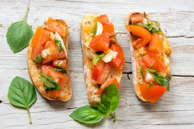 Bruscheta, antipasti típico italiano con tomate, albahaca y tostadas.