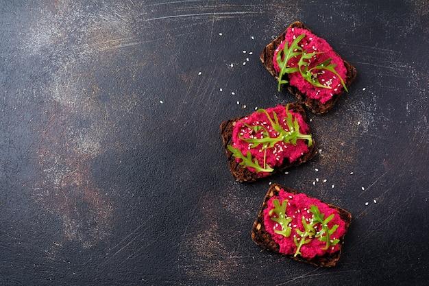 Bruschetta con hummus de remolacha, rúcula y semillas de sésamo sobre una superficie de hormigón oscuro