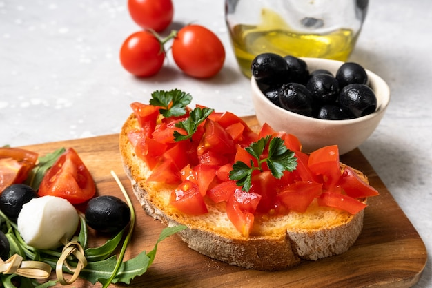 Bruschetta italiana con tomate, aceite de oliva, perejil verde. entrante de antipasti típico italiano en restaurante en italia roma milán.