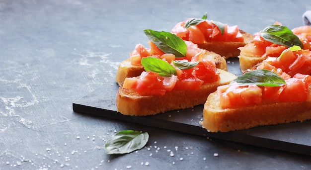 Bruschetta italiana con tomate y albahaca sobre una pizarra negra