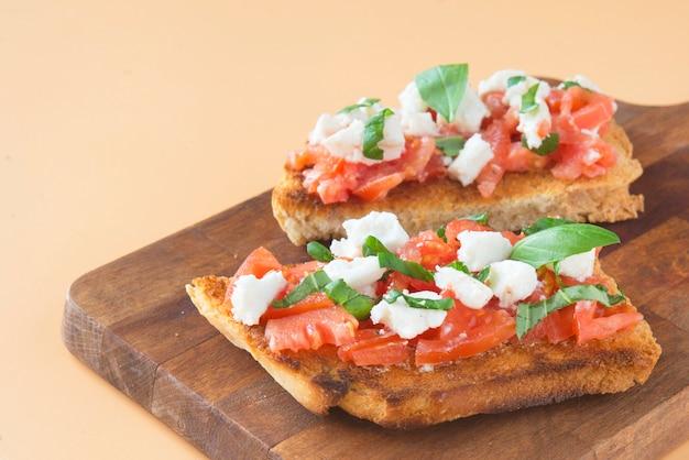 Bruschetta italiana con tomate, queso mozzarella y albahaca