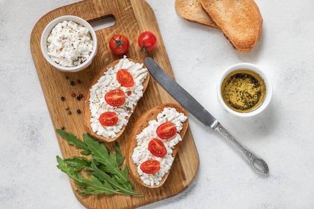 Bruschetta italiana con tomates asados, queso mozzarella y hierbas sobre una tabla para cortar.