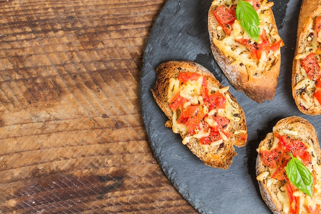 Bruschetta italiana con tomates asados, queso mozzarella y