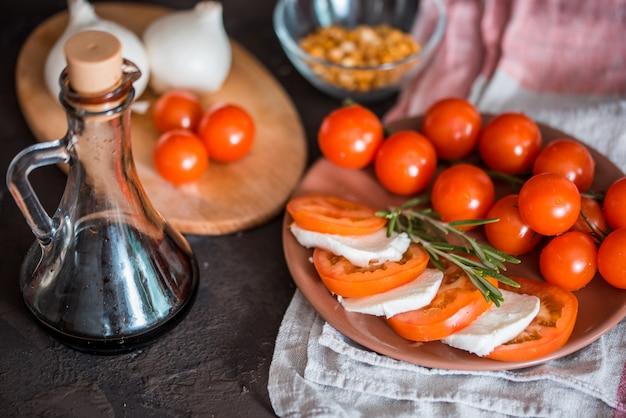 Bruschetta italiana con tomates picados, albahaca, queso mozzarella y vinagre balsámico. bruschetta o crostini e ingredientes caprese hechos en casa frescos en el fondo negro, espacio de la copia.